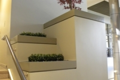 Artificial Boxwood and Japanese Red Maple surrounded by river rock in stairway planters